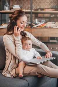 Mother smiling and working at home while taking care of her son. Home business concept